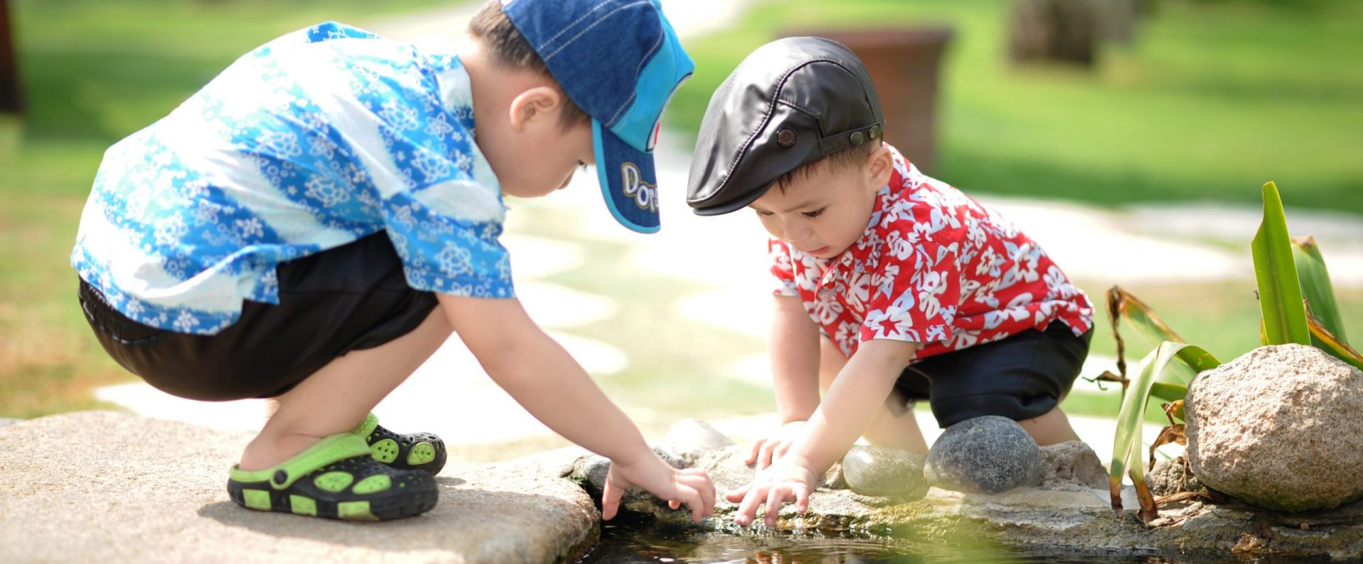 Canva - Boy in Blue and White Shirt Playing Near on Body of Water With Boy in Red Shirt